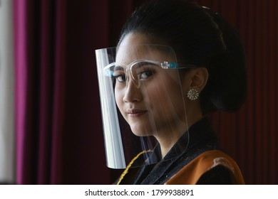 Bojonegoro, Indonesia, August , 19, 2020. a woman in Javanese traditional clothes using a face shileld as a form of implementing a health protocol to combat the Covid-19 pandemic