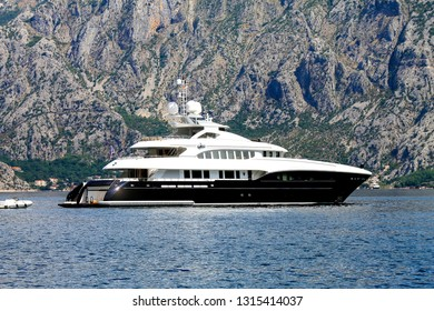 Boka Kotor , Montenegro. White luxury yacht sailing on the Bay of Kotor on the background of high mountains in Montenegro.