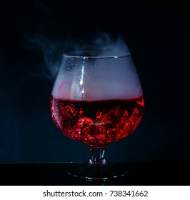 bokals with a red cocktail with an unusual effect of smoke