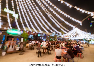 Bokeh background of Street Bar beer restaurant, outdoor in asia, People sit chill out and hang out dinner and listen to music together in Avenue, Happy life ,work hard play hard