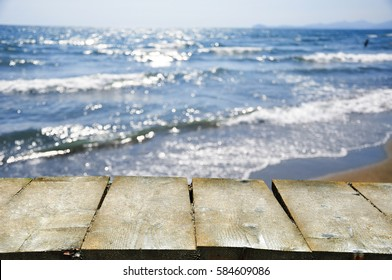 Bokeh of beatiful sea beach with waves and with wooden table in the foreground for product placement