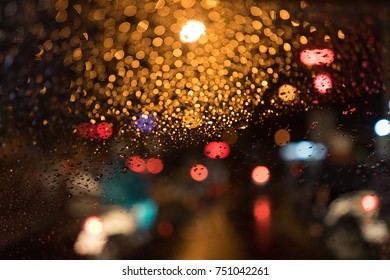 Bokeh Blur of Defocused Street Lights through Rain Drops on Car Windshield Glass Window in glowing colorful night driving city scene with abstract yellow, red, blue and green circular background