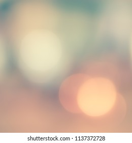 Bokeh blurred background city night blurry abstract light party in vintage style warm pastel pink yellow gold and faded cool blue mint green color