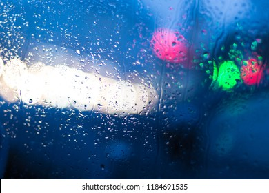 Bokeh from illumination of fires of the night city through glass of the car and a rain. Drops of a rain flow down on glass. Indistinct focus