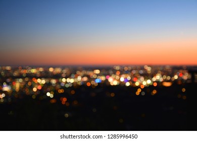 Bokeh lights of a city at sunset.