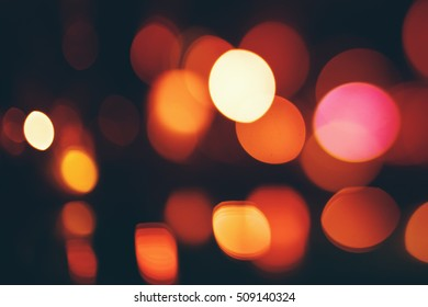 Bokeh lights on dark background. Defocused blurred lights. Yellow and red colors.