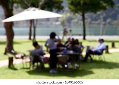 The bokeh photo of leisure time at dining table with friend or family on the park of lakeside.
