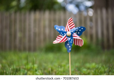 Bokeh photo of a pinwheel with America flag stars and stripes.