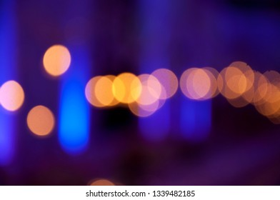 Bokeh photograph of party lights giving an ambient blue, black and golden effect.