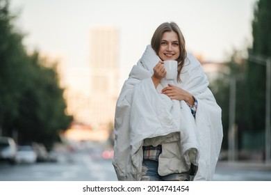 Bokeh portrait of a woman wrapped in blanket drinking coffee over city background. Early in the morning.