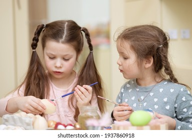 Bokeh shapes, selective focus, special blur, two girls with bunny ears are painting Easter eggs, children are preparing for the spring holiday, Easter mood.