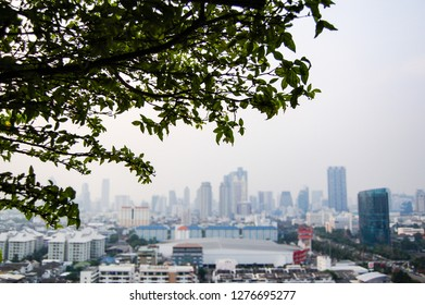 Bokeh of a tree with background of the blurred skyscrapers in downtown Bangkok, the capital of Thailand in southeast Asia, with bright sky on a sunny day in horizontal view.