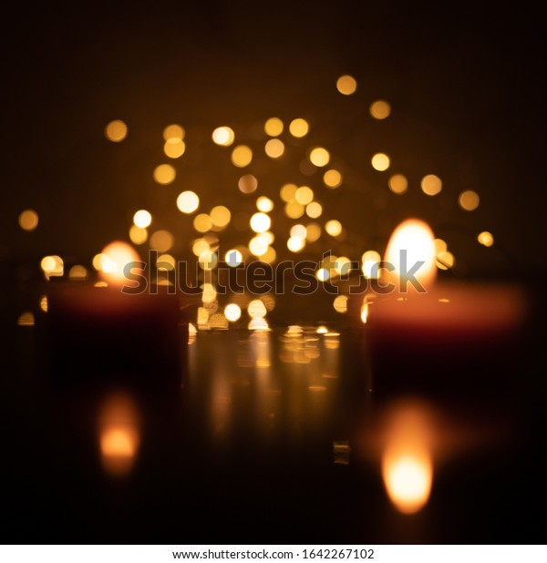 Bokeh of two candles on a background of yellow LED lights