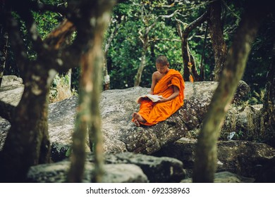 Bokor, Kampot, Cambodia - March 1, 2017: Cambodian Buddhist reads a book under a tree, near a temple on a hill in Bokor National Park in Cambodia