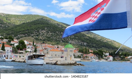 Bol / Brac Island / Croatia - July 17, 2016: Passenger boats near the lighthouse in Bol (and the pier where the catamaran arrives and leaves from). Croatia flag waving.