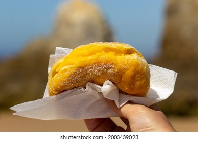 Bola de Berlim, or Berlim Ball, a Portuguese pastry made from a fried donut filled with sweet eggy cream and rolled in crunchy sugar. it's very traditional to eat on the beach