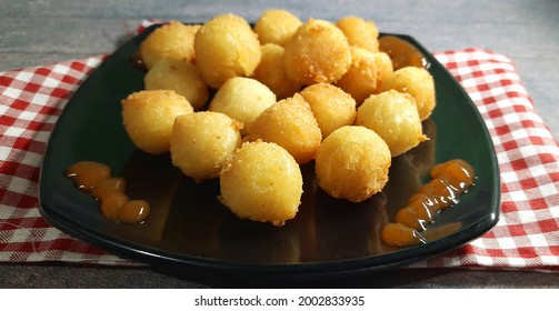 Bola-bola kentang keju or pom pom kentang  or mashed potatoes cheese balls is served on black plate
