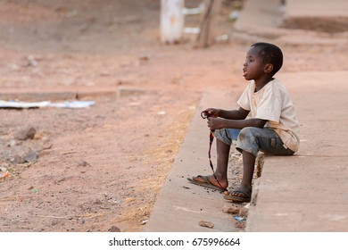 BOLAMA ISLAND, GUINEA BISSAU - MAY 6, 2017: Unidentified local little boy sits beside the road in the ghost town of Bolama, the former capital of Portuguese Guinea
