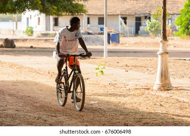 BOLAMA ISLAND, GUINEA BISSAU - MAY 6, 2017: Unidentified local man rides a bicycle along the street in the ghost town of Bolama, the former capital of Portuguese Guinea