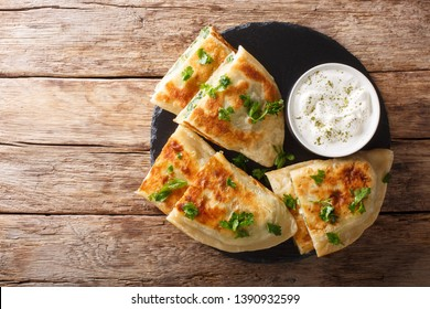 Bolani flat-bread from Afghanistan, baked or fried with a vegetable filling and served with plain yogurt closeup on the table. horizontal top view from above