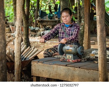 bolaven plateau, laos - november 23, 2018: woman produces knives on simple machines.
