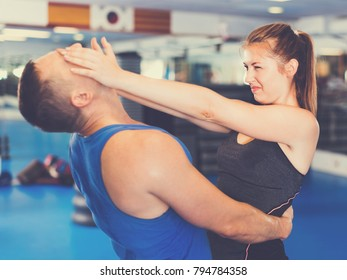 Bold  cheerful  woman is training with man on the self-defense course in gym.
