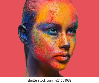 Bold color fantasy. Holi festival of colors background. Female face art with creative make up. Closeup studio portrait of young fashion model isolated on peach pink background