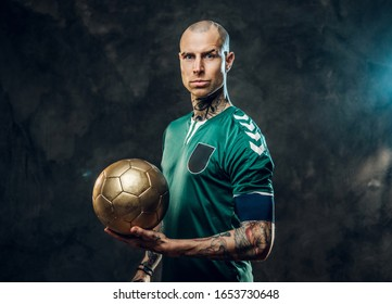 Bold and handsome soccer player posing for a photoshot in a dark studio, wearing green professional sportswear, and holding a golden soccer ball looking serious and focused