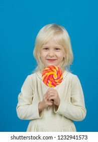 Bold hard candy creation. Small child with sweet lollipop. Small girl hold lollipop on stick. Happy candy girl. Happy childhood food.