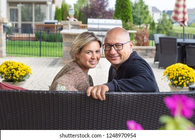 Bold man in glasses and black sweater and woman with short blond hair sitting on sofa, looking back turned to camera and smiling, sitting on open terrace with green garden in background