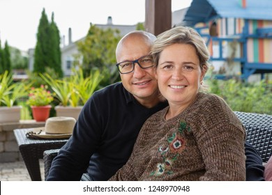 Bold man in glasses and woman with short haircut in casual sweater sitting close on sofa on terrace of cafe, hotel or residential house, looking at camera and smiling. Family portrait concept