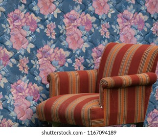 Bold striped chair with a loud flower patterned mattress behind it makes for clashing patterns and colors