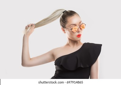 Bold stylish beautiful and trendy. Girl woman with flourish floral flower glasses combined with coral pastel lipstick, black one shoulder dress pulling her ponytail hair on white grey background wall