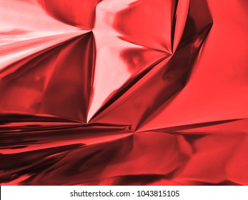 Bold vibrant Holographic iridescent and shimmering red color wrinkled foil. Hologram background of wrinkled abstract foil texture with colors and shiny background. Good for christmas cards.
