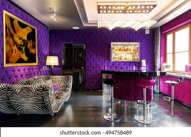 Bold violet and pink colours in the room with striped couch