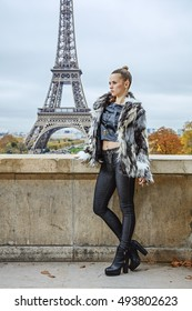 Bold winter in Paris. Full length portrait of modern fashion-monger in fur coat in Paris, France looking into the distance