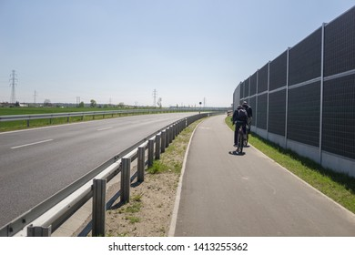 Boleslawiec, Poland April 2019 unidentified people cycle on the cycling path alongside bypass-road surrounded by the noise barriers, acoustic screens
