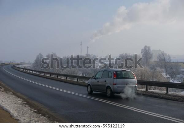 Boleslawiec, Poland February 2017 car goes through the smogged city and makes smoke in Boleslawiec, Poland in February 2017