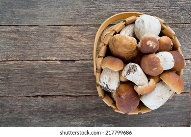 boletus mushrooms in a basket on wooden surface