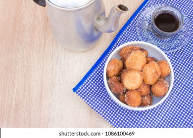 Bolinho de Chuva with cinnamon and sugar and a cup of coffe. A kind of brazilian typical food. It's a fried cookie/cake cooked by grandmas. It's a dessert that represents childhood in Brazil.