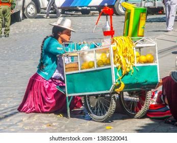 BOLIVIA, LA PAZ, 24 JULY 2008: Street orange juice woman seller with small carriage in La Paz, Bolivia, South America.