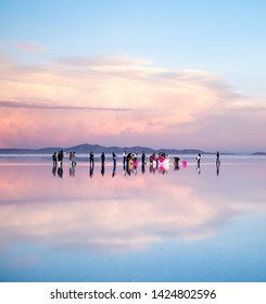 Bolivia - October 21, 2018: Wedding ceremony with fiance and bride walking on the surface of largest mirrored salt flats