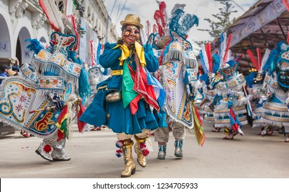 Bolivia, Oruro carnival with dancers performing wearing masks and traditional dresses on the street during the carnival procession
