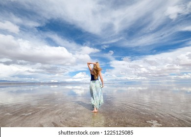 Bolivia. Salt Lake Uyuni. A blonde girl walks back in the water in a long skirt, the sky hops in the water, a natural Mirror. Clear day