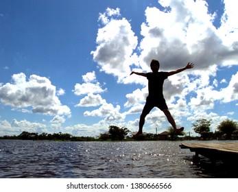 Bolivia, Trinidad - April 19, 2014 : One male jumping to the peaceful Laguna Suarez lake with beautiful sunny blue sky and cloud with sun light
