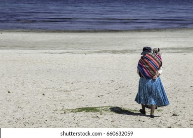 Bolivian woman with her baby in the back walking in the sand on the Island of the Sun