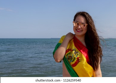 Bolivian woman on the beach with flag of Bolivia