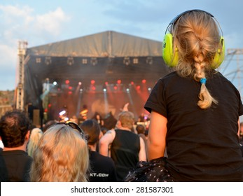 BOLKOW, POLAND - JULY 18, 2014: Child with protection earphones during concert at the Castle Party dark independent festival. Castle  Party is annual festival with the gothic, rock and electro music.