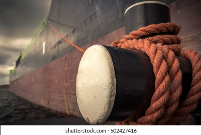 Bollard with mooring ropes. The vessel is moored alongside a big ship. Retro/vintage style.