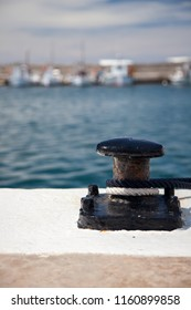 Bollard with ropes in a marina with small fishing boats in the background